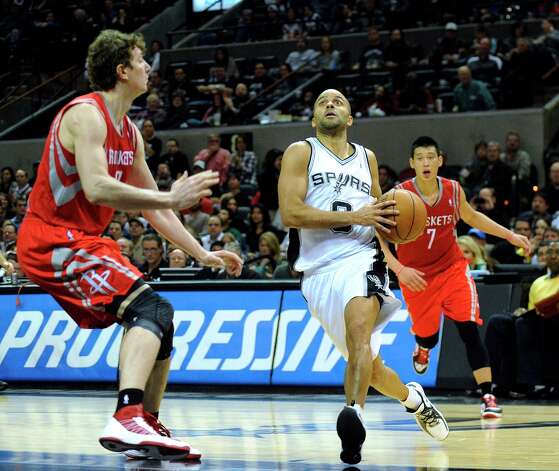 Spurs guard Tony Parker drives for two of his 31 points as Omer Asik (left) and Jeremy Lin of the Rockets defend during second-half action at the AT&T Center on Friday, Dec. 28, 2012. Photo: Billy Calzada, San Antonio Express-News / SAN ANTONIO EXPRESS-NEWS