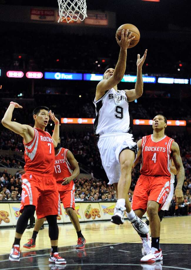 Tony Parker of the Spurs shoots a reverse layup as Jeremy Lin (7) and Greg Smith (4) of the Rockets defend at the AT&T Center on Friday, Dec. 28, 2012. Photo: Billy Calzada, San Antonio Express-News / SAN ANTONIO EXPRESS-NEWS