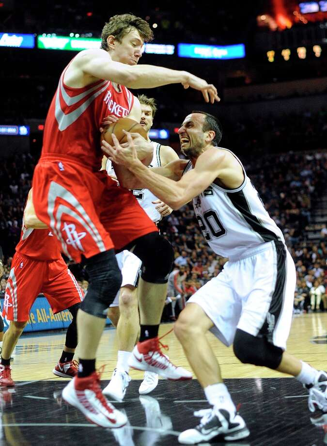 Manu Ginobili of the Spurs is fouled by Omer Asik of the Rockets during first-half action at the AT&T Center on Friday, Dec. 28, 2012. Photo: Billy Calzada, San Antonio Express-News / SAN ANTONIO EXPRESS-NEWS