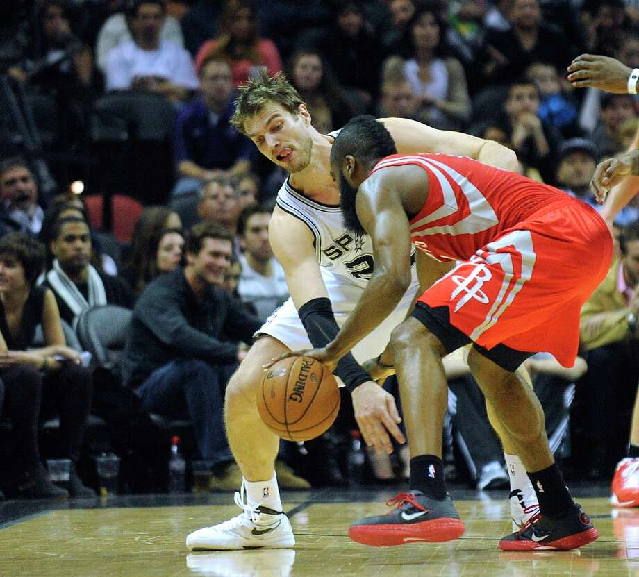 Tiago Splitter of the Spurs ties up James Harden of the Rockets during second-half action at the AT&T Center on Friday, Dec. 28, 2012. Photo: Billy Calzada, San Antonio Express-News / SAN ANTONIO EXPRESS-NEWS