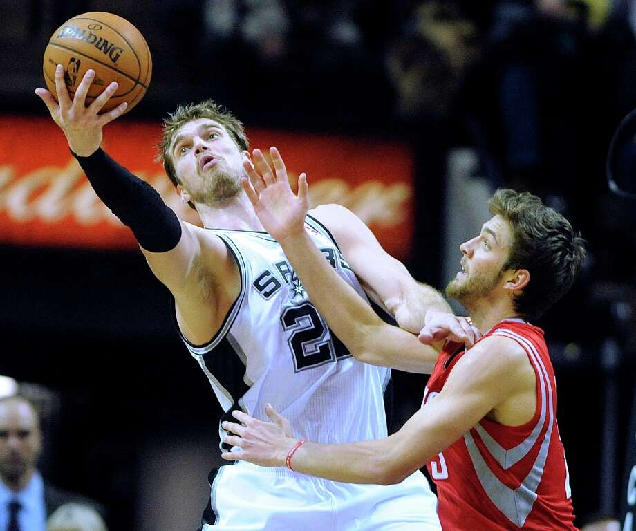 Tiago Splitter of the Spurs rebounds as Omer Asik of the Rockets reaches during second-half action at the AT&T Center on Friday, Dec. 28, 2012. San Antonio won, 122-116. Photo: Billy Calzada, San Antonio Express-News / SAN ANTONIO EXPRESS-NEWS