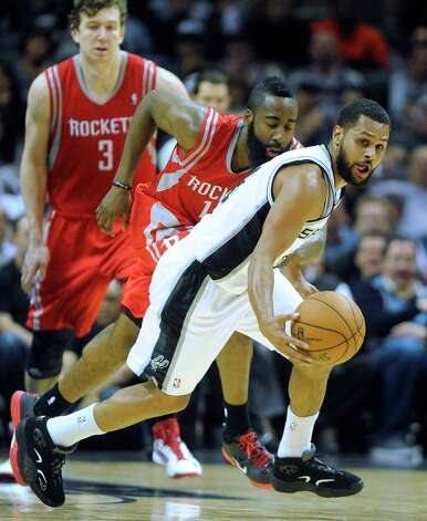 Patty Mills of the Spurs grabs a loose ball as James Harden and Omer Asik (3) of the Rockets follow at the AT&T Center on Friday, Dec. 28, 2012. Photo: Billy Calzada, San Antonio Express-News / SAN ANTONIO EXPRESS-NEWS