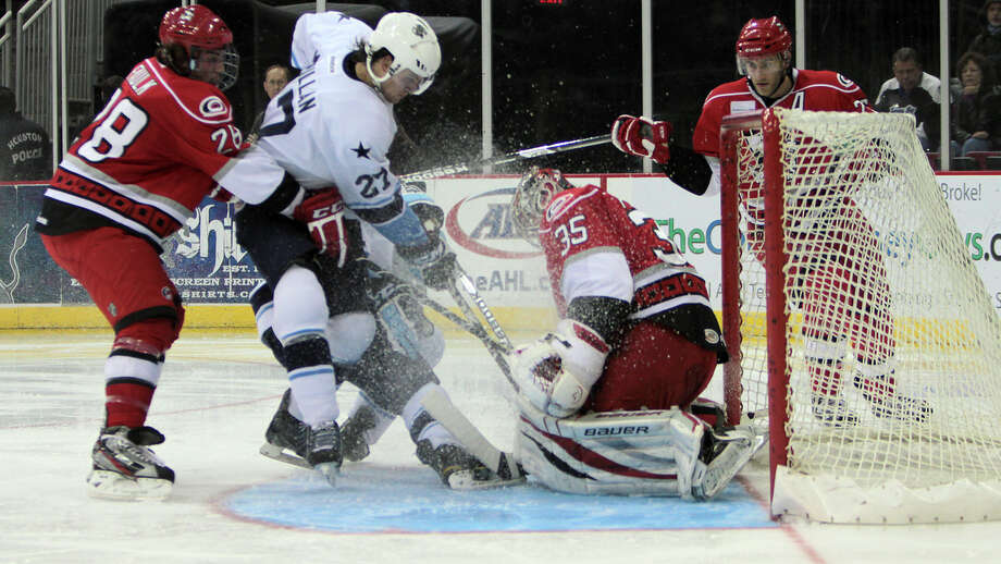 Aeros center Carson McMillan tries to get the puck past Checkers goalie Justin Peters during Friday night's divisional clash.