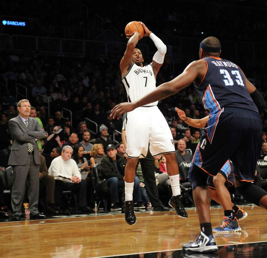 Brooklyn Nets interim coach P.J. Carlesimo watches as Joe Johnson (7) shoots over the Bobcats' Brendan Haywood (33) in the first half Friday. Photo: Kathy Kmonicek, FRE / FR170189 AP