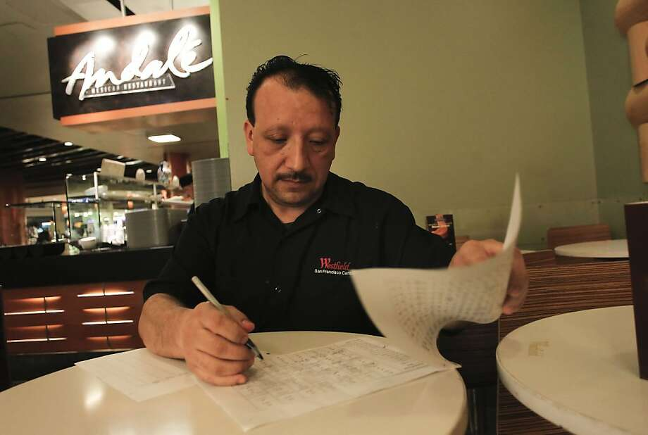 Temo Elvira fills out the work schedule for the people he supervises in the kitchen at the Westfield mall. Photo: Michael Macor, The Chronicle