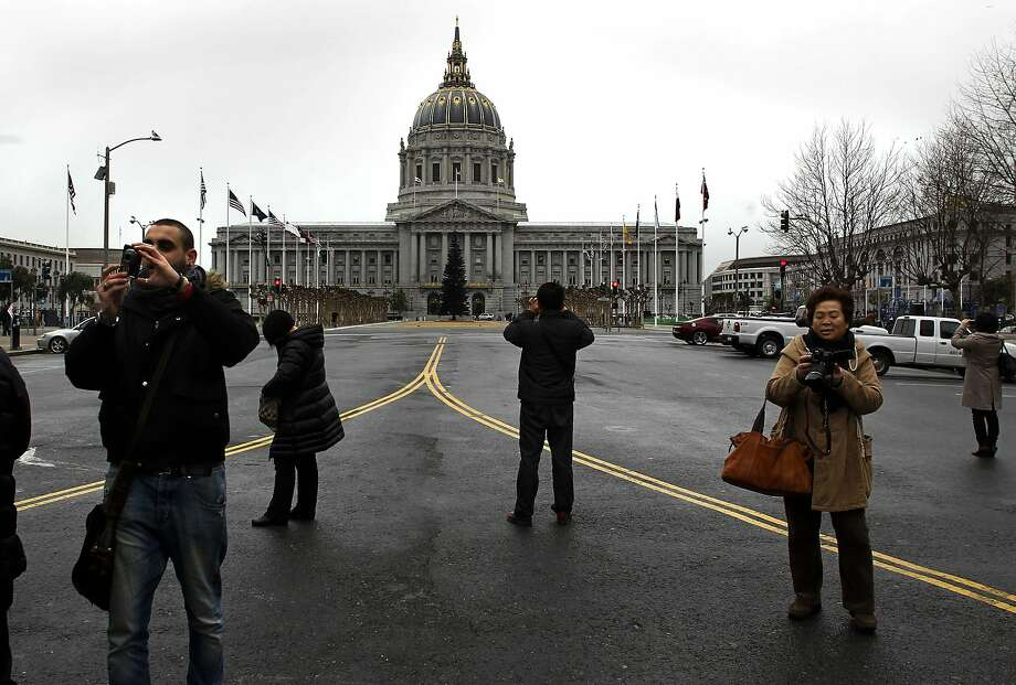 Tourists stop to take in the sites in and around Civic Center Plaza in San Francisco, Calif. on Friday Dec. 28, 2012. In 2008, former Mayor Gavin Newsom talked of transforming Civic Center into a global model for sustainability with living roofs, solar panels, and water reclamation projects. But critics say his vision has failed to materialize since he left office and that the current administration is settling for pedestrian projects like more efficient toilets and sinks. Photo: Michael Macor, The Chronicle