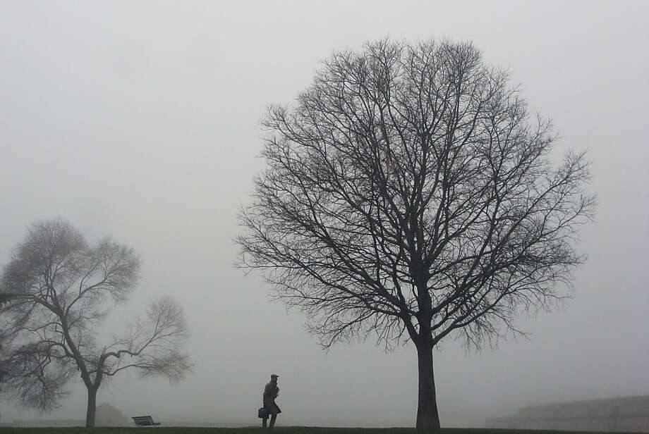 A man walks between tress at Vuelta del Castillo park, as the fog covers the landscape, in Pamplona, northern Spain, Friday, Dec. 28, 2012. Photo: Alvaro Barrientos, Associated Press