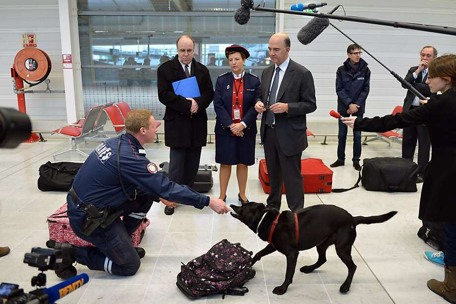 French Minister of the Economy, Finance and Foreign Trade, Pierre Moscovici (4th L) listens to a customs officer's explanations on the sniffer dogs' tasks during his visit to the French customs service at Orly's international airport, in Orly, near Paris, on December 28, 2012.  Photo: Miguel Medina, AFP/Getty Images