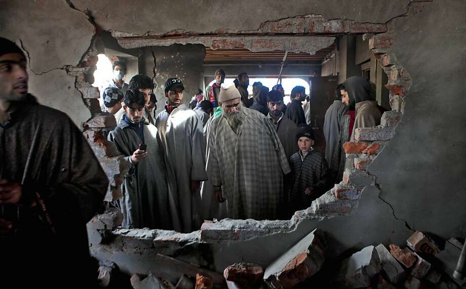 Kashmiri villagers inspect a damaged house after a gun battle in Chandigam, a village 45 kilometers (30 miles) south of Srinagar, India, Friday, Dec. 28 , 2012. Indian forces on Friday killed two suspected rebels in a gun battle and wounded seven civilians later during anti-India protests in southern Kashmir, police said. Photo: Dar Yasin, Associated Press