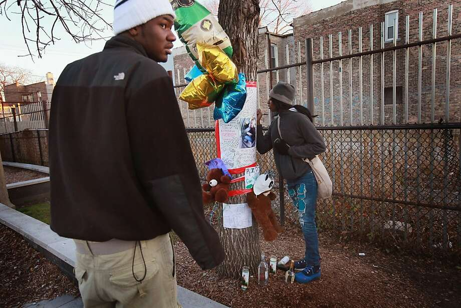 Eighteen-year old Samantha Boyd (R) and 19-year-old Marcell Carter sign a memorial to their friend, 16-year-old Jeffrey Stewart in the play lot where Stewart collapsed after being shot on December 9, in the Humboldt Park neighborhood on city's West Side December 11, 2012 in Chicago, Illinois. Stewart was shot about a block away then ran to the playground where he collapsed. Stewart was shot along with 17-year-old Anton Reed who survived with a gunshot wound to the hand. Reed was later arrested after vomiting three baggies of what appeared to be cocaine. Chicago has had about 500 murders this year. Today after news organizations began reporting about what was believed to be the 500th murder the Chicago Police Department's News Affairs Office issued a statement stating Chicago's murder total remains at 499 because classification of one death investigation remains pending. They would not specify which death is pending. The total number of murders in the city has only once exceeded 500 victims since 2004.  The murder rate is up about 11 percent from 2011, much of which is attributed to growing gang violence. Photo: Scott Olson, Getty Images