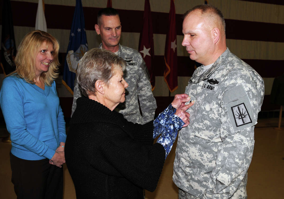DIVISION OF MILITARY AND NAVAL AFAIRS Cindy Hopek, left, and Maj. Gen. Patrick Murphy, in back, look on as her mother, Alice Snyder, pins a one star general?s rank onto her brother and Snyder?s son, Raymond Shields, during Shields? promotion to brigadier general in Latham.