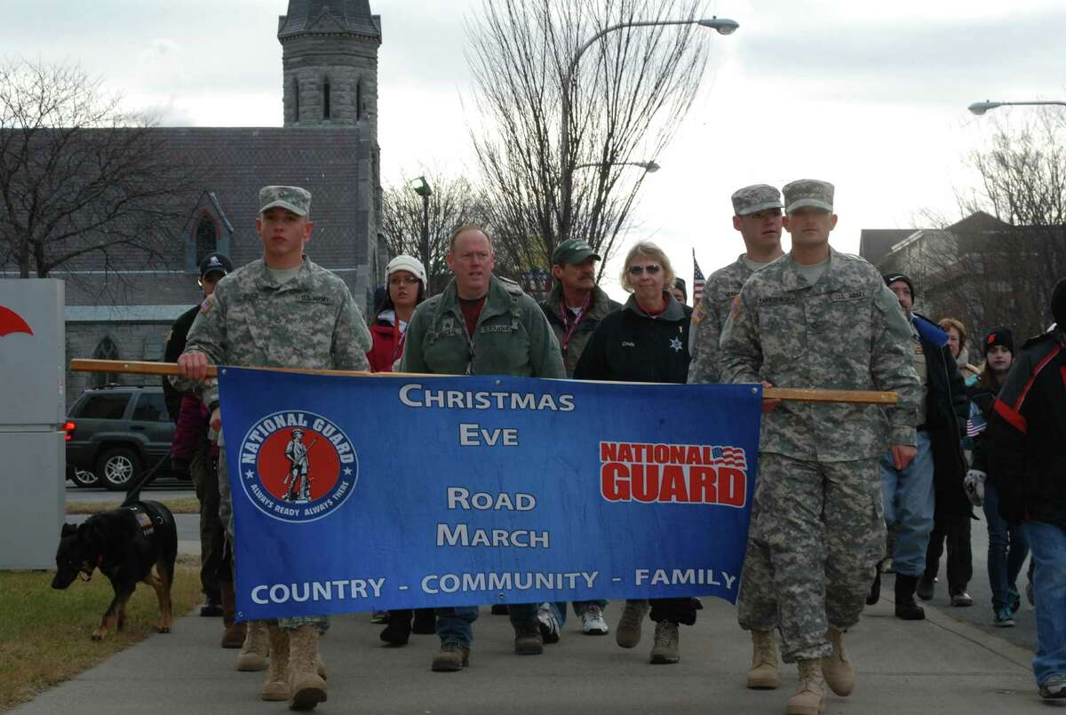 COL. RICHARD GOLDENBERG / DIVISION OF MILITARY AND NAVAL AFFAIRS New York Army National Guard Pfc. Tyler Bruce, from left, Jacob Zabrzewski and Pfc. Matthew Herrick carry a banner at the start of the ninth annual Christmas Eve road march in Glens Falls.