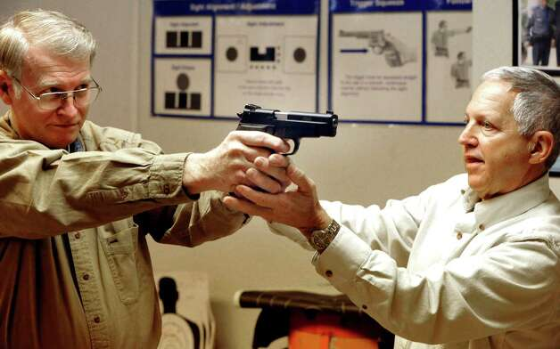 Paul Murphy, left, is instructed in proper gripping and aiming of a semi-automatic pistol by Herb Furhman during an National Rifle Association-approved basic pistol safety course in New Milford Saturday, Dec. 29, 2012. Photo: Michael Duffy / The News-Times