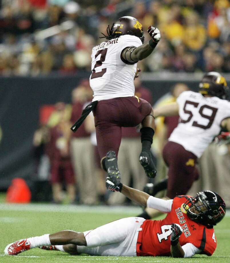 Minnesota kick returner Troy Stoudermire (2) jumps over Texas Tech's Derrick Mayes during the first quarter of his Meineke Car Care Bowl college football game, Friday, Dec. 28, 2012, in Reliant Stadium in Houston. Photo: Nick De La Torre, Houston Chronicle / © 2012  Houston Chronicle