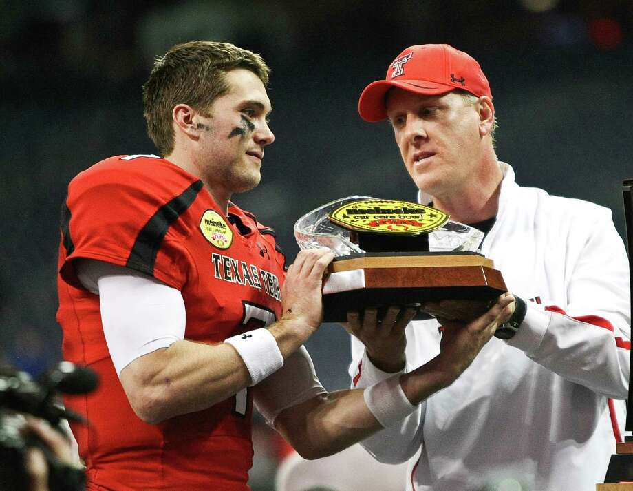 Texas Tech interim head coach Chris Thomsen, right, hands the Meineke Car Care Bowl trophy to quarterback and game MVP Seth Doege, Saturday, Dec. 29, 2012, in Reliant Stadium in Houston.  Texas Tech won 34-31. Photo: Nick De La Torre, Houston Chronicle / © 2012  Houston Chronicle