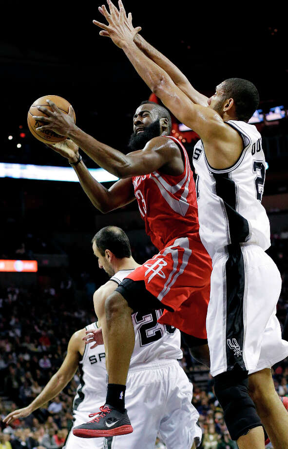 James Harden, left, shoots under Spurs defender Tim Duncan. Photo: Eric Gay, Associated Press / AP