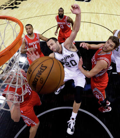Manu Ginobili (20), of Argentina, is fouled as he drives to the basket against Rockets defenders Cole Aldrich (31), Daequan Cook (14), James Harden (13) and Chandler Parsons, right, during the fourth quarter. Photo: Eric Gay, Associated Press / AP