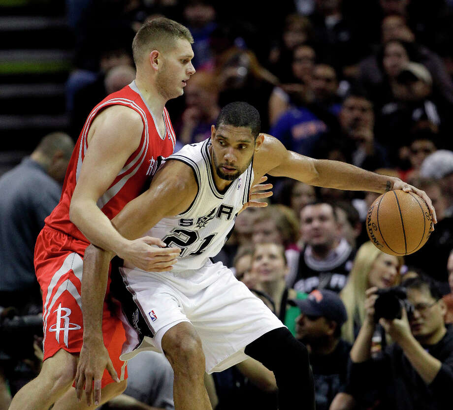 Tim Duncan, right, works the ball around Rockets defender Cole Aldrich. Photo: Eric Gay, Associated Press / AP