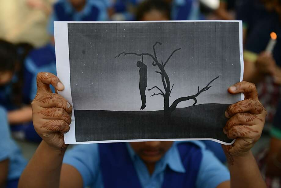 Indian schoolgirl holds a placard with an image of a hanging man during a rally in Ahmedabad on December 29, 2012, after the death of a gangrape victim from the Indian capital New Delhi. Indian leaders appealed for calm and security forces headed off fresh unrest by turning New Delhi into a fortress after a student who was savagely gang-raped died in a Singapore hospital. Police threw a ring of steel around the centre of the Indian capital after news of the 23-year-old medical student's death was broken in the early hours by the Singapore hospital that had been treating her for the last two days.  Photo: Sam Panthaky, AFP/Getty Images