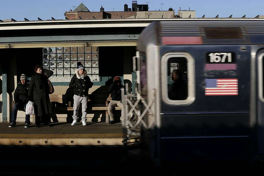 Commuters watch as a train enters the 40th St-Lowry St Station, where a man was killed after being pushed onto the subway tracks, in the Queens section of New York, Friday, Dec. 28, 2012. Police are searching for a woman suspected of pushing the man and released surveillance video Friday of her running away from the station.(AP Photo/Seth Wenig) Photo: Seth Wenig, Associated Press