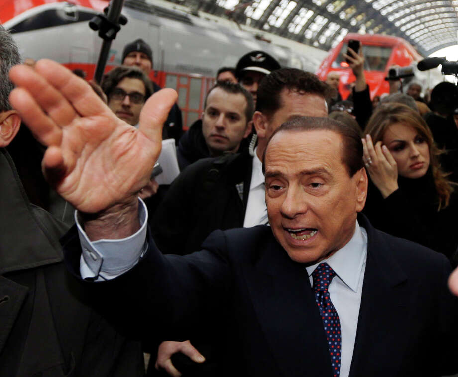 "Former Italian premier Silvio Berlusconi arrives at Milan's central train station, Italy, Saturday, Dec. 29, 2012. Italian Premier Mario Monti announced Friday he is heading a new campaign coalition made of up centrists, business leaders and pro-Vatican forces who back his ""ethical"" vision of politics, aiming for a second mandate in office if his fledging reform movement wins big in parliamentary elections. Monti was appointed premier 13 months ago after his scandal-plagued predecessor Silvio Berlusconi failed to stop Italy from sliding deeper into the eurozone debt crisis. He quit earlier this month after Berlusconi pulled his party's support from Monti's government, but is now continuing in a caretaker role until the next elections. (AP Photo/Luca Bruno) Photo: Luca Bruno"