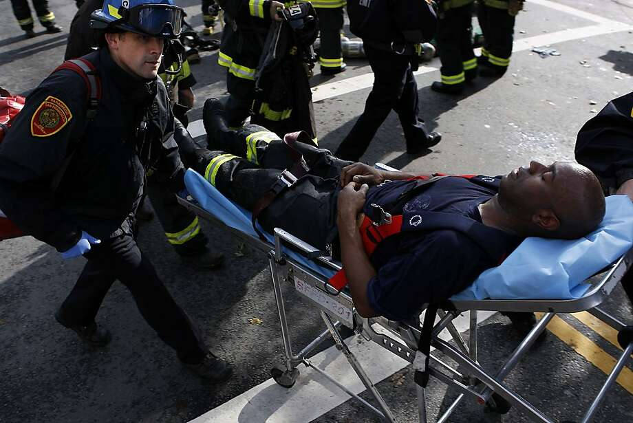 Medics care for a firefighter at the site of the blaze in the Mission District. Photo: Sean Havey, The Chronicle