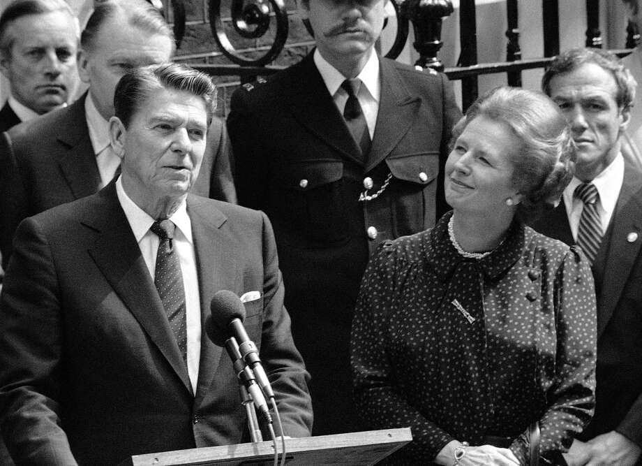 FILE - In this June 9, 1982 file photo, Britain's Prime Minister Margaret Thatcher, right, smiles with satisfaction as President Ronald Reagan makes a farewell speech outside her Downing Street office in London prior to his departure for Bonn. It is not often that the president of the United States needs to seek fashion advice. But when Ronald Reagan was getting ready for a visit to England as a guest of Queen Elizabeth II in June 1982, his people had an important question for the Brits: Just what does one wear to go riding with the queen in the magnificent horse country surrounding Windsor Castle? The answer: Something smart, but casual, of course. Riding boots, breeches and a turtleneck sweater would do fine _ no need for formal riding attire.  The fashion inquiry is but one tidbit contained in nearly 500 pages of formerly Confidential documents relating to the Reagan visit being made public Friday, Dec. 28, 2012 by Britain's National Archives. (AP Photo/Bob Dear, File) Photo: Bob Dear