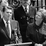 FILE - In this June 9, 1982 file photo, Britain's Prime Minister Margaret Thatcher, right, smiles with satisfaction as President Ronald Reagan makes a farewell speech outside her Downing Street office in London prior to his departure for Bonn. It is not often that the president of the United States needs to seek fashion advice. But when Ronald Reagan was getting ready for a visit to England as a guest of Queen Elizabeth II in June 1982, his people had an important question for the Brits: Just what does one wear to go riding with the queen in the magnificent horse country surrounding Windsor Castle? The answer: Something smart, but casual, of course. Riding boots, breeches and a turtleneck sweater would do fine _ no need for formal riding attire.  The fashion inquiry is but one tidbit contained in nearly 500 pages of formerly Confidential documents relating to the Reagan visit being made public Friday, Dec. 28, 2012 by Britain's National Archives. (AP Photo/Bob Dear, File)
