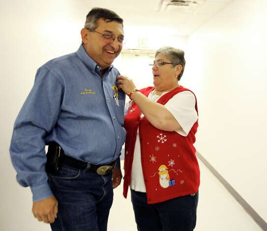 Zapata County Sheriff Sigifredo Gonzalez, Jr. gets his shirt adjusted by his wife, Carmen, before a retirement tamalada, Thursday, Dec. 13, 2012. Gonzalez will retire at the end of the year after nearly 19 years in office. He first ran for sheriff in 1992, losing in a runoff election to incumbent Romeo Ramirez. Gonzalez said that at the time he thought that was the end of his political career. Two years later, Ramirez was arrested on corruption charges and Gonzalez, at the time the chief investigator for the county attorney, was appointed to replace him. Photo: Jerry Lara, San Antonio Express-News / © 2012 San Antonio Express-News