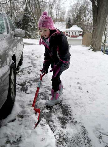 Michelle Wallack, 7, helps her father shovel snow off their Stamford driveway on Saturday, December 29, 2012. Photo: Lindsay Niegelberg, Niegelberg / Stamford Advocate