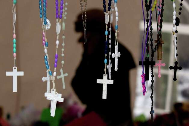 Rosaries dangle from a cross as part of a memorial to the victims of the Sandy Hook school shooting Thursday, Dec. 27, 2012, in Newtown. Handmade items made from a variety of mediums dot the landscape of the many makeshift memorials for the 26 victims of the Sandy Hook Elementary school shooting. ( Brett Coomer /  ) Photo: Brett Coomer, Brett Coomer/Hearst Newspapers / The News-Times