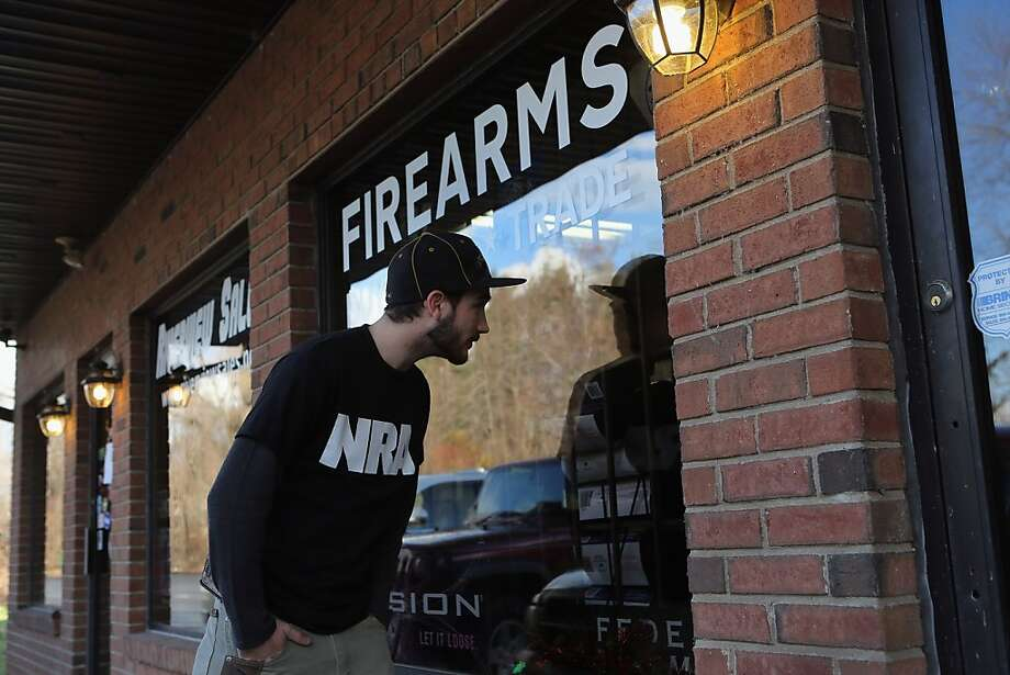 An NRA member looks in the window of a closed gun shop in East Windsor, Conn., this month. Photo: John Moore, Getty Images