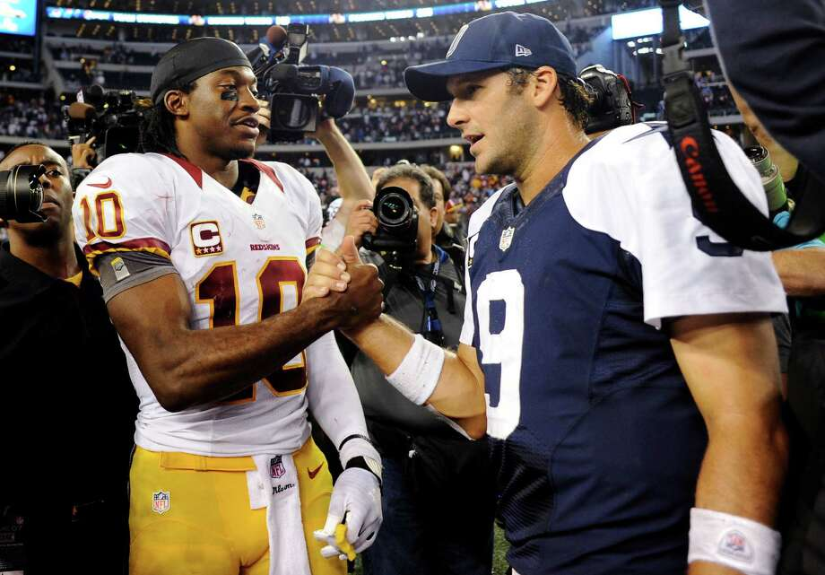 ADVANCE FOR WEEKEND EDITIONS, DEC. 29-30 - FILE - In this Nov. 22, 2012, file photo, Washington Redskins quarterback Robert Griffin III (10) and Dallas Cowboys quarterback Tony Romo (9) greet after the Redskins won 38-31 in an NFL football game in Arlington, Texas. The Cowboys and  Redskins have played 103 times, but rarely have the stakes been this high. On Sunday, the winner gets the NFC East. The loser stays home for the playoffs, or maybe gets a wild card berth if things go just right.  (AP Photo/Matt Strasen, File) Photo: Matt Strasen, Associated Press / FR170476 AP