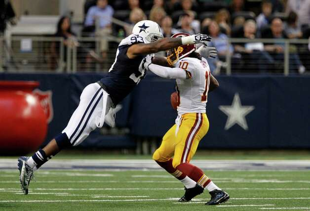 Dallas Cowboys' Anthony Spencer (93) attempts to tackle Washington Redskins quarterback Robert Griffin III (10) during an NFL football game Thursday, Nov. 22, 2012, in Arlington, Texas. The Redskins won 38-31. (AP Photo/Tim Sharp) Photo: Tim Sharp, Associated Press / FR62992 AP