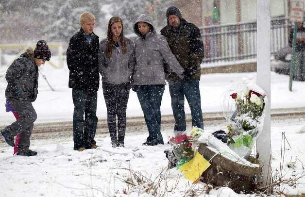 A group of people gather around at the site where a makeshift memorial once stood near Sandy Hook Elementary School Saturday, Dec. 29, 2012, in Newtown. Two of the main memorials have been taken down, leaving just a few items left at the site. ( Brett Coomer / Hearst Newspapers ) Photo: Brett Coomer, Brett Coomer/Hearst Newspapers / The News-Times