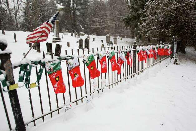 Christmas stockings remain on the fence near Sandy Hook Cemetary near the site of a makeshift memorial for the victims of the Sandy Hook school shooting Saturday, Dec. 29, 2012, in Newtown. Two of the main memorials have been taken down, leaving just a few items left at the site. ( Brett Coomer / Hearst Newspapers ) Photo: Brett Coomer, Brett Coomer/Hearst Newspapers / The News-Times