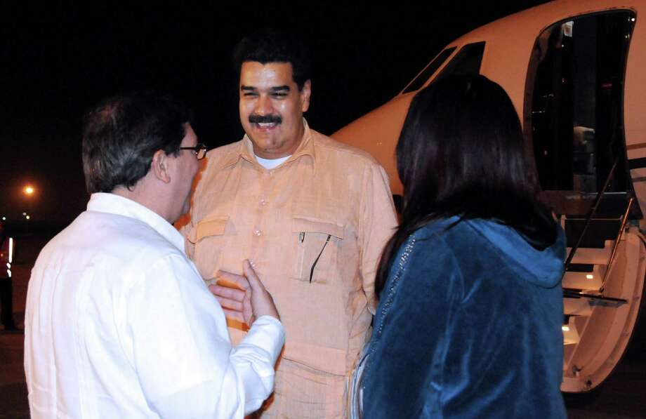 In this photo provided by Cuba's state newspaper Granma, Cuban Foreign Minister Bruno Rodriguez , left, talks with Venezuela's Vice President Nicolas Maduro, center, as Venezuelan Attorney General Cilia Flores watches at the Jose Marti International Airport in Havana on Saturday, Dec. 29, 2012. Maduro arrived in Cuba to visit Venezuelan President Hugo Chavez, who is recovering from a surgery_ his fourth operation related to his pelvic cancer since June 2011. (AP Photo/Granma, Juvenal Balan Neyra ) Photo: Juvenal Balan Neyra, HO / Granma
