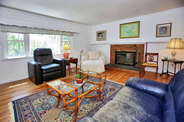 The living room has a yellow brick fireplace with a raised hearth topped with a slate slab. Photo: Contributed Photo/Granite Studio