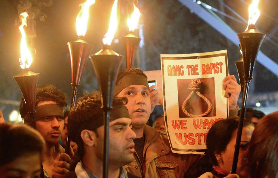Indian protestors hold torches and placards during a rally in New Delhi on December 29, 2012, after the death of a gang rape student from the Indian capital.  Indian leaders appealled for calm fearing fresh outbursts of protests after the death of a gang-rape student victim. New Delhi's top police officer and chief minister have urged people to mourn the death of a gang-rape victim in a peaceful manner as large parts of the city-centre were sealed off. The calls for calm came after an Indian woman who was gang-raped on a New Delhi bus died in a Singapore hospital after suffering severe organ failure.  AFP PHOTO/RAVEENDRANRAVEENDRAN/AFP/Getty Images Photo: RAVEENDRAN, AFP/Getty Images / AFP