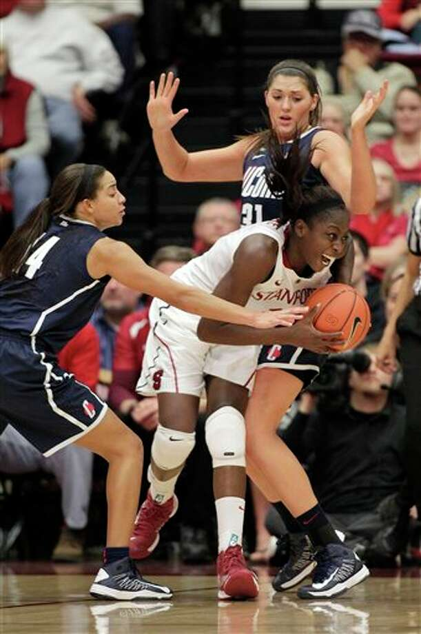 Stanford forward Chiney Ogwumike, center, is doubled-teamed by UConn center Stefanie Dolson, right, and guard Bria Hartley during the first half of an NCAA college basketball game in Stanford, Calif., Saturday, Dec. 29, 2012. (AP Photo/Tony Avelar)
