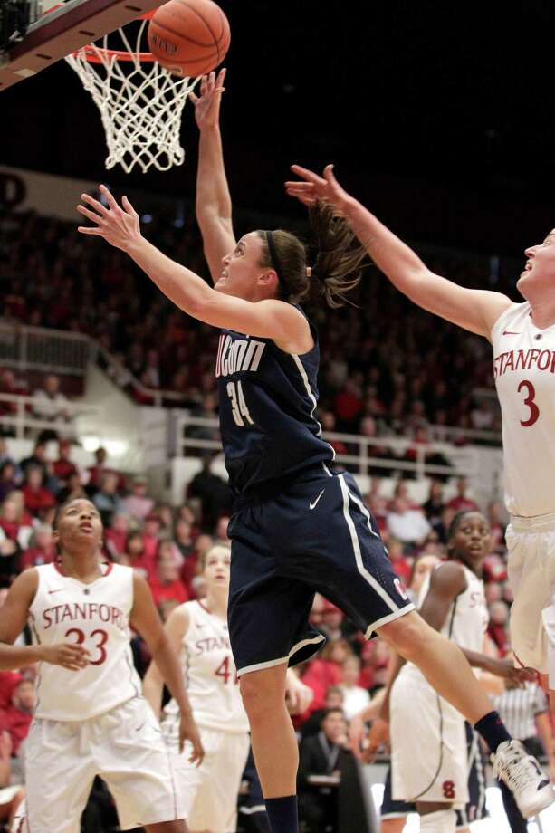 Connecticut guard Kelly Faris (34) drives to the basket against Stanford forward Mikaela Ruef (3) as guard Jasmine Camp (23) looks on during the first half of an NCAA college basketball game in Stanford, Calif., Saturday, Dec. 29, 2012. (AP Photo/Tony Avelar) Photo: Tony Avelar, Associated Press / FR155217 AP