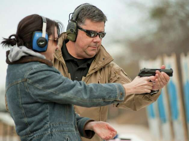 Firearms instructor Russell King, right, teaches pre-school teacher Heather Miller during concealed handgun license training, Saturday, Dec. 29, 2012, at Lone Star Handgun in San Antonio. Photo: Darren Abate, Express-News