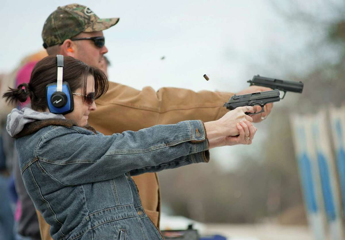 Preschool teacher Heather Miller and her husband, elementary school administrator Jason Miller, practice firing during training at LoneStar Handgun in San Antonio.
