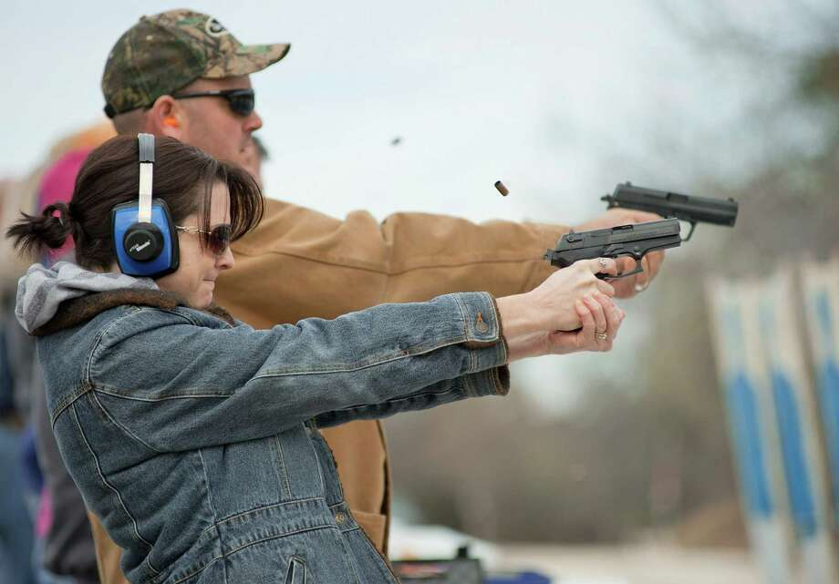 Preschool teacher Heather Miller and her husband, elementary school administrator Jason Miller, practice firing during training at LoneStar Handgun in San Antonio. Photo: Darren Abate, Express-News