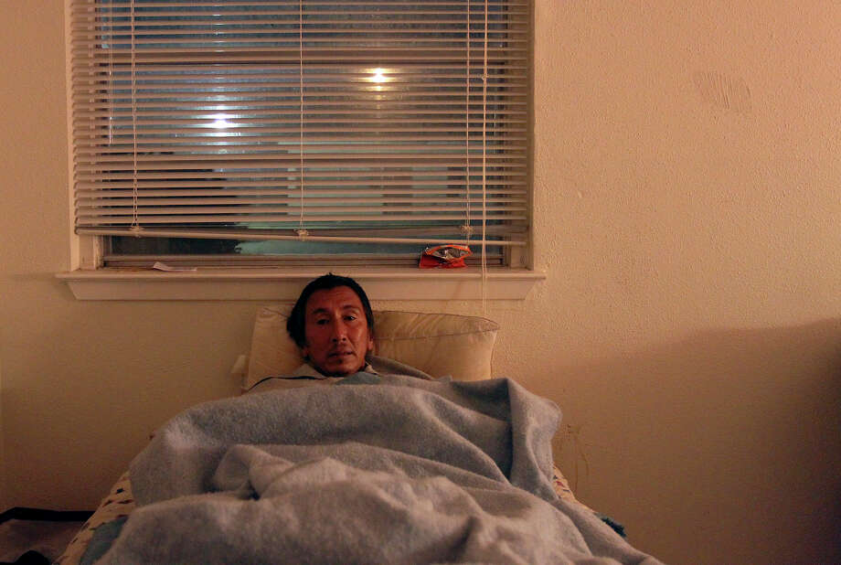 Raul Morales, who has been living in a boarding home for about a year, gets ready for bed. Photo: Kin Man Hui, San Antonio Express-News / ©2012 San Antonio Express-News
