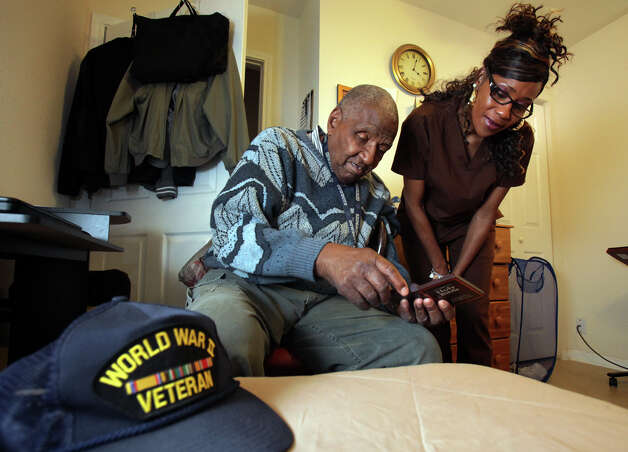 Boarding home owner Gina Ellison helps one of her residents, Marion Runnels, find a Scripture on his electronic Bible. Photo: Bob Owen, San Antonio Express-News / © 2012 San Antonio Express-News