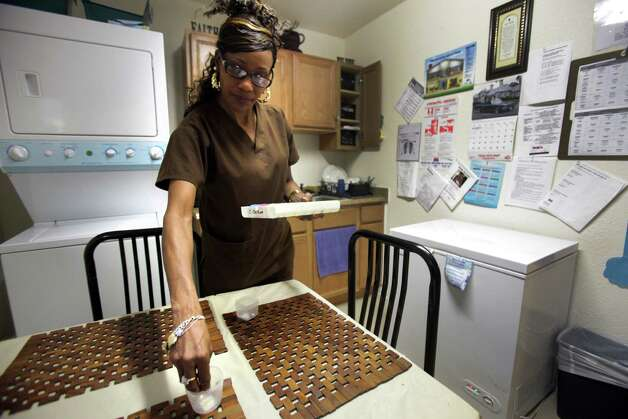Gina Ellison, owner of Christian Hope Personal Care Home, places her client's medicine in small cups to be taken before dinner. Tuesday, Dec. 11, 2012. Photo: Bob Owen, San Antonio Express-News / © 2012 San Antonio Express-News