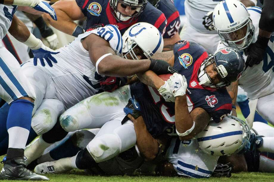 Houston Texans running back Arian Foster (23) is brought down by Indianapolis Colts defensive end Cory Redding (90) as he goes off tackle for a two-yard gain inside the Colts red zone during the first quarter at Reliant Stadium on Sunday, Dec. 16, 2012, in Houston. Photo: Smiley N. Pool, Houston Chronicle / © 2012  Houston Chronicle