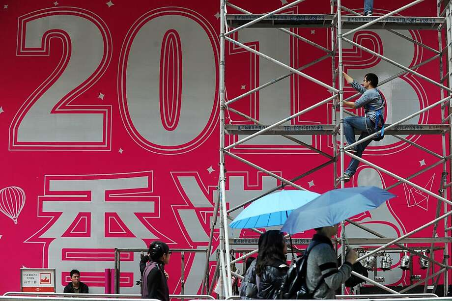 A worker (top R) climbs up a scaffolding support in front of a promotional 2013 banner ahead of the new years eve celebrations outside a shopping mall in Hong Kong on December 29, 2012. The mall, a popular New Year countdown venue, is preparing for the upcoming celebrations where they expect thousands of people to attend. Photo: Anthony Wallace, AFP/Getty Images