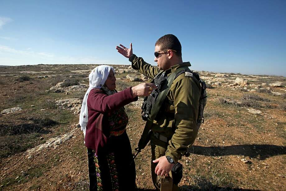 A Palestinian woman disputes with an Israeli soldier as they evacuate Palestinian land owners trying to farm on their land near the Jewish settlement of Sosia, in the village of Yatta south of the West Bank city of Hebron on December 29, 2012. Palestinian farmers are restricted from cultivating their land in the disputed area near the city of Hebron due to the Israeli settlements and military zone nearby. Photo: Hazem Bader, AFP/Getty Images